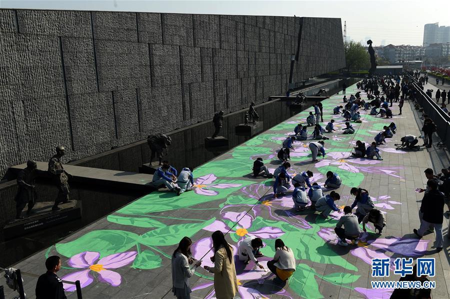 """用美术颜料手绘紫金草图案,将和平之花""""种植""""在纪念馆雕塑广场的地面"""