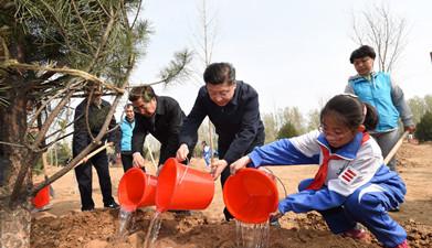 习近平同大家一起给刚栽下的树苗浇水