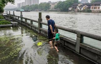 京杭大运河水位上涨 杭州市民下水捞鱼