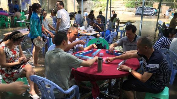 重庆局地40℃高温 民众水中打牌吃饭消暑纳凉