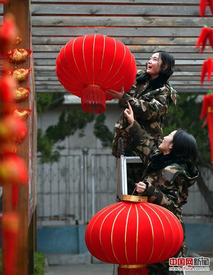 1月19日,山东烟台女子边防派出所女兵们利用大红灯笼,窗花等装扮警营