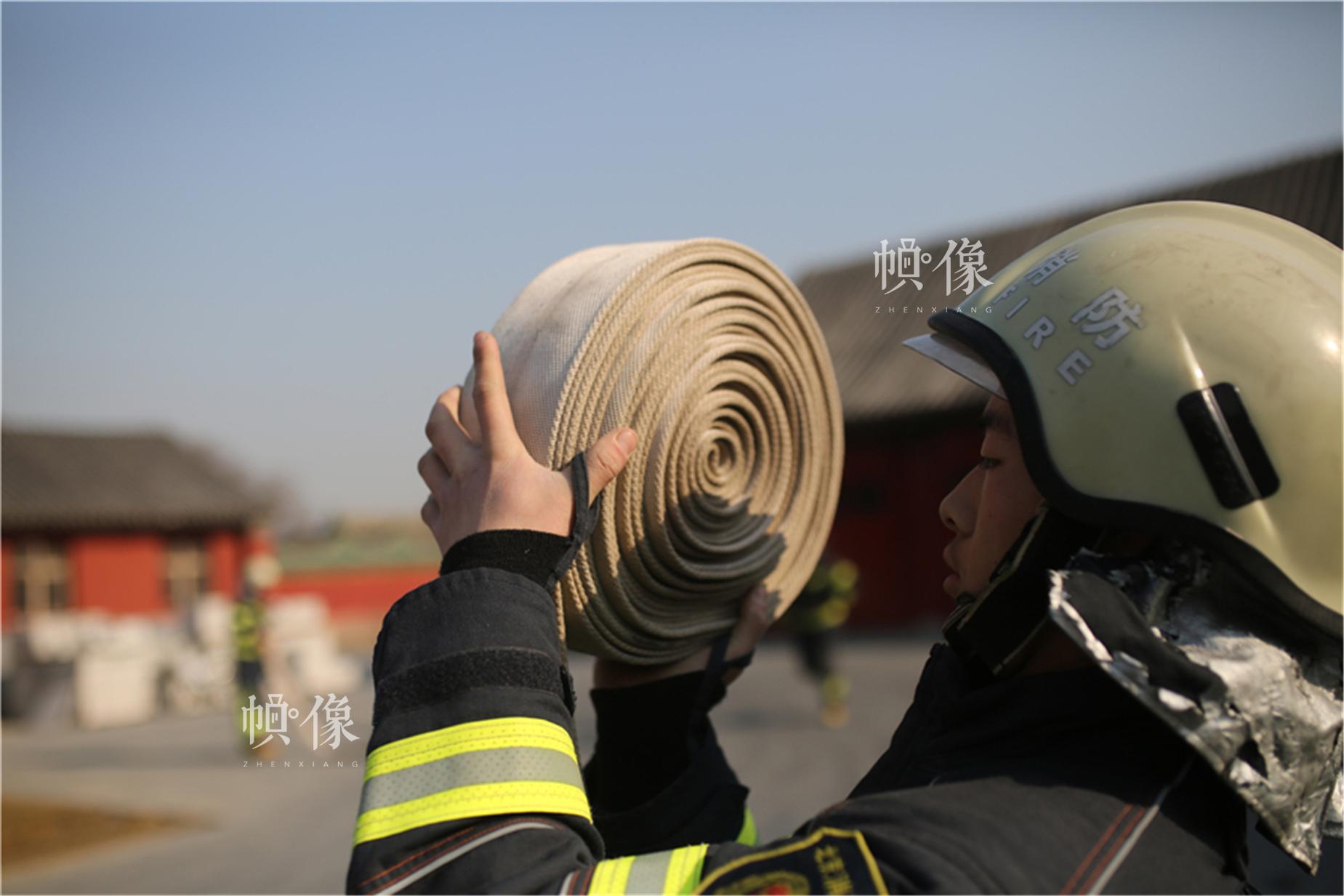 消防队员演习中收卷消防水带。