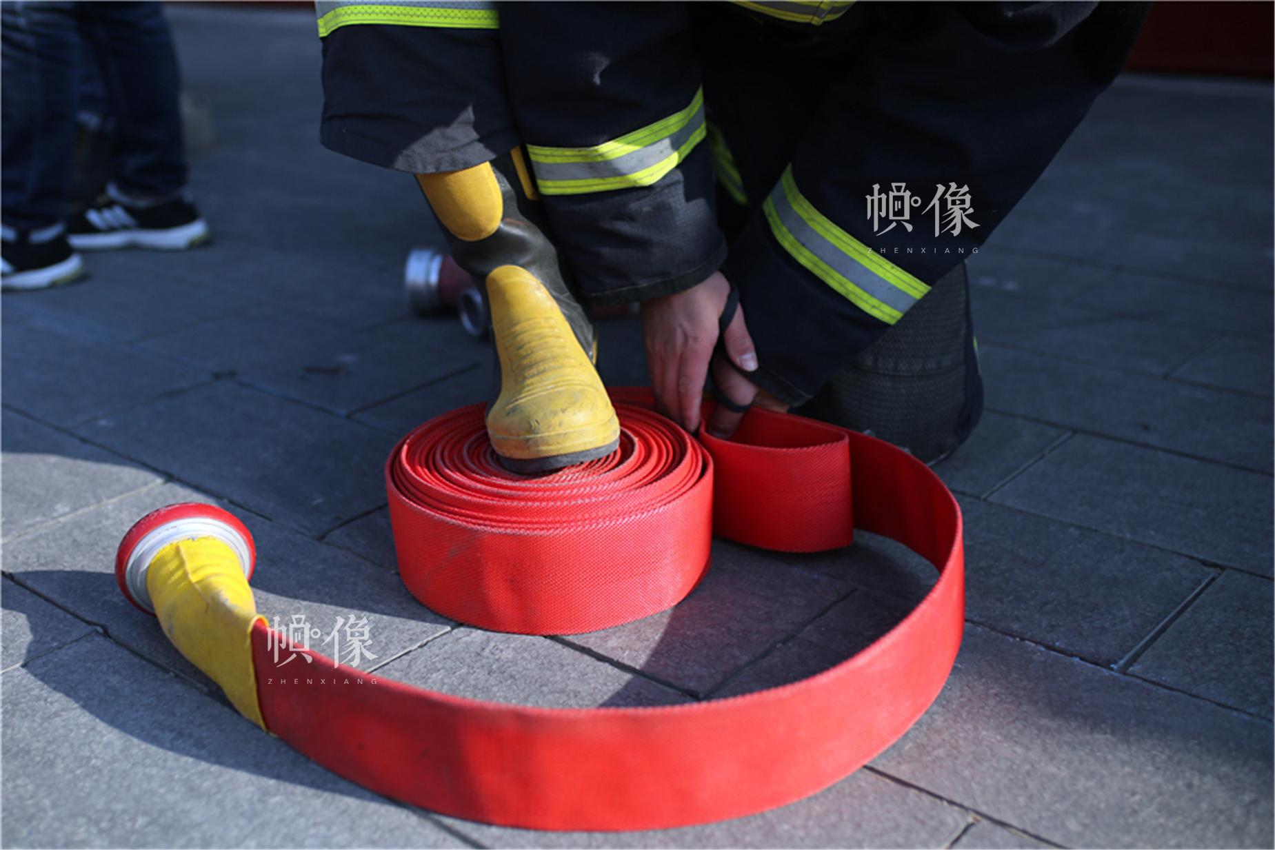 消防队员收紧消防水带。