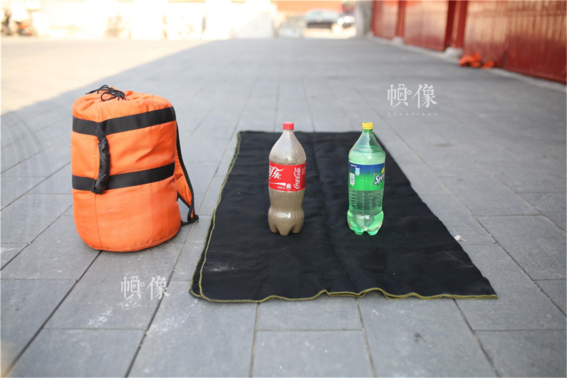 消防战士自己发明的便携式灭火消防包,里面装有一个灭火毯、一瓶沙子和一瓶水,可以随时处置火情。