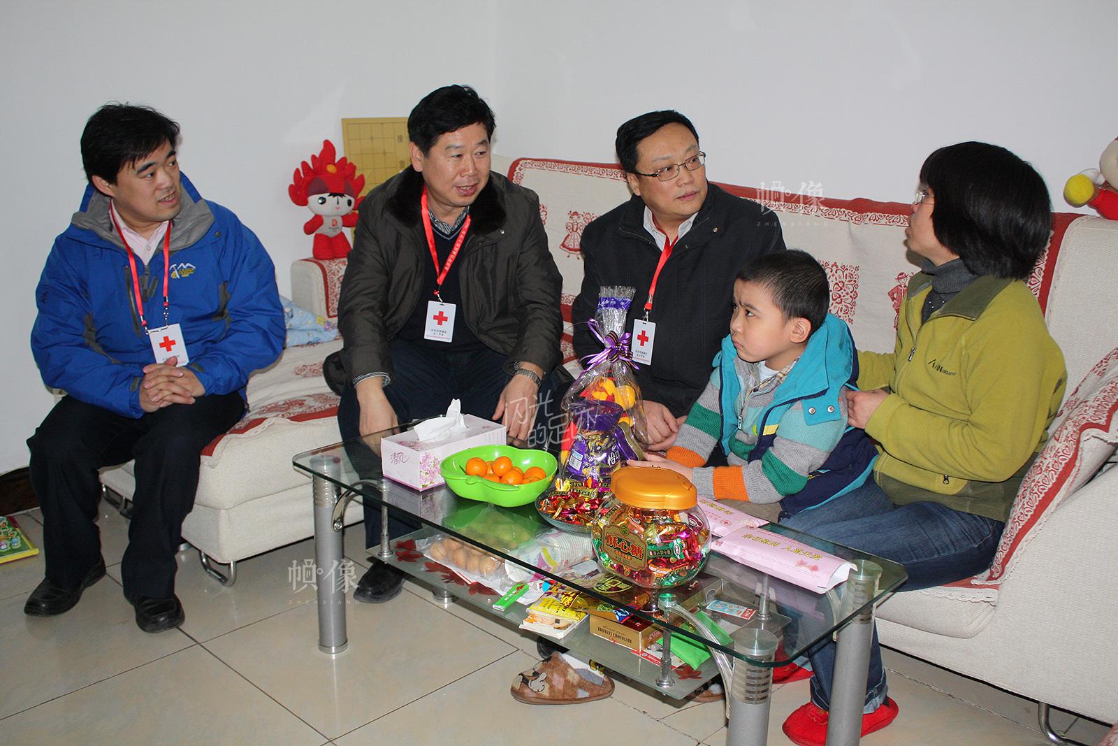 2014年,两节期间北京市西城区红十字会入户慰问大病患儿。(北京市西城区红十字会供图)