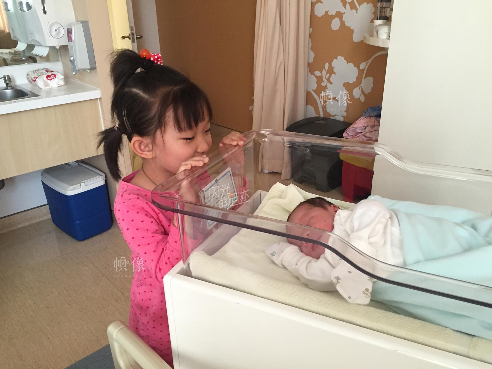 """2016年5月,老二宋星延出生,老大宋雨润看着刚出生的弟弟。(图片由""""二孩""""父母提供)"""