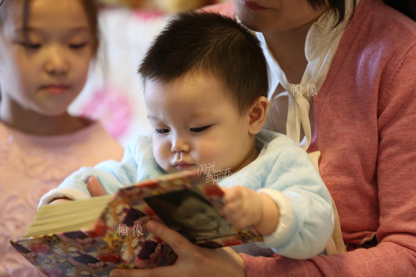 老二宋星延在妈妈怀抱里和姐姐一起看妈妈小时候的照片。中国网记者 黄富友 摄