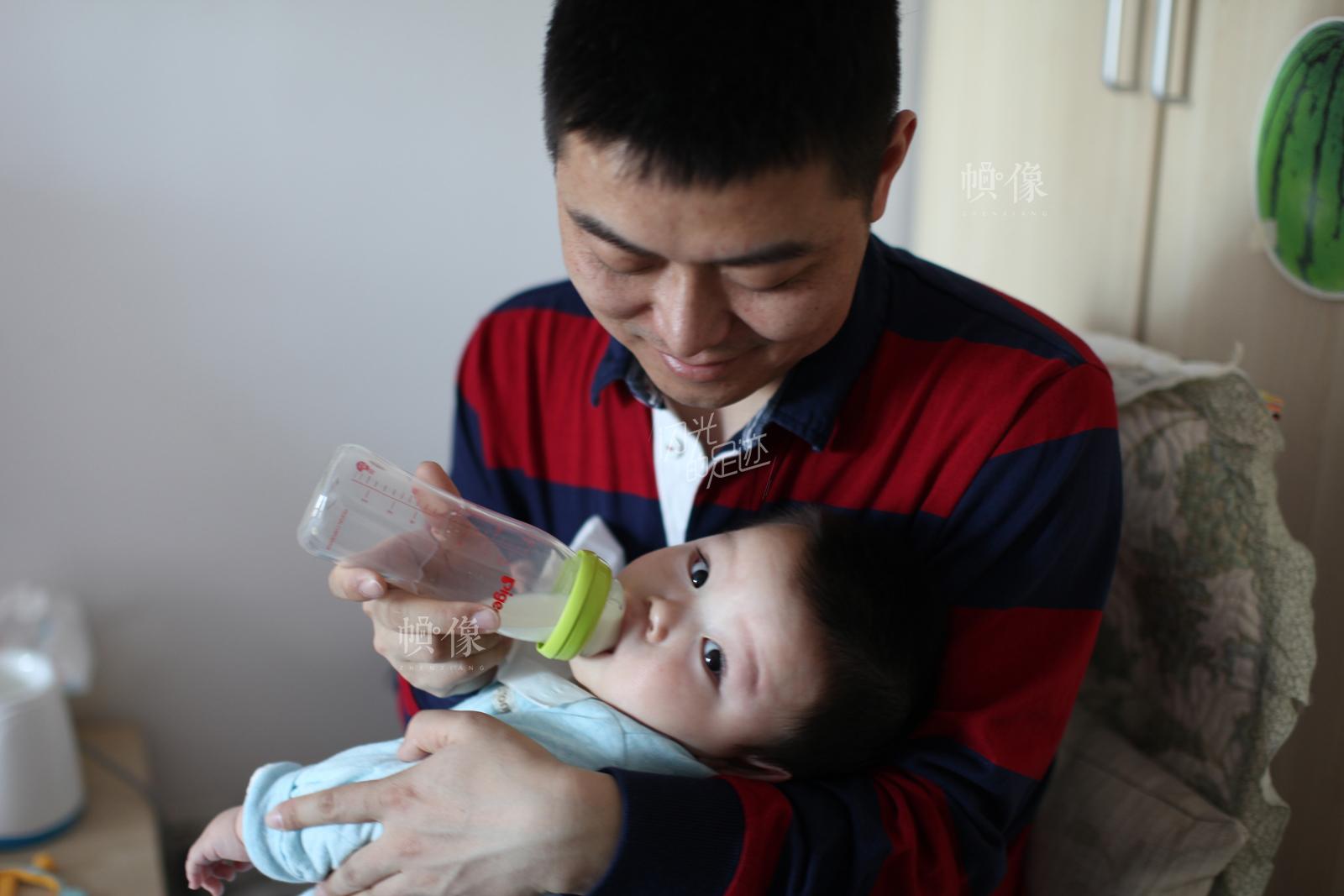 下午休息时间,爸爸宋栋给老二喂奶。 中国网记者 赵超 摄