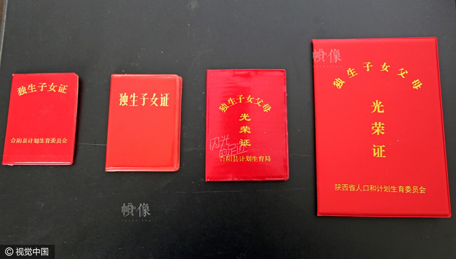 2016年12月16日,陕西渭南合阳县城区机关计划生育办公室,工作人员展示独生子女证颁发以来的四代证。 视觉中国