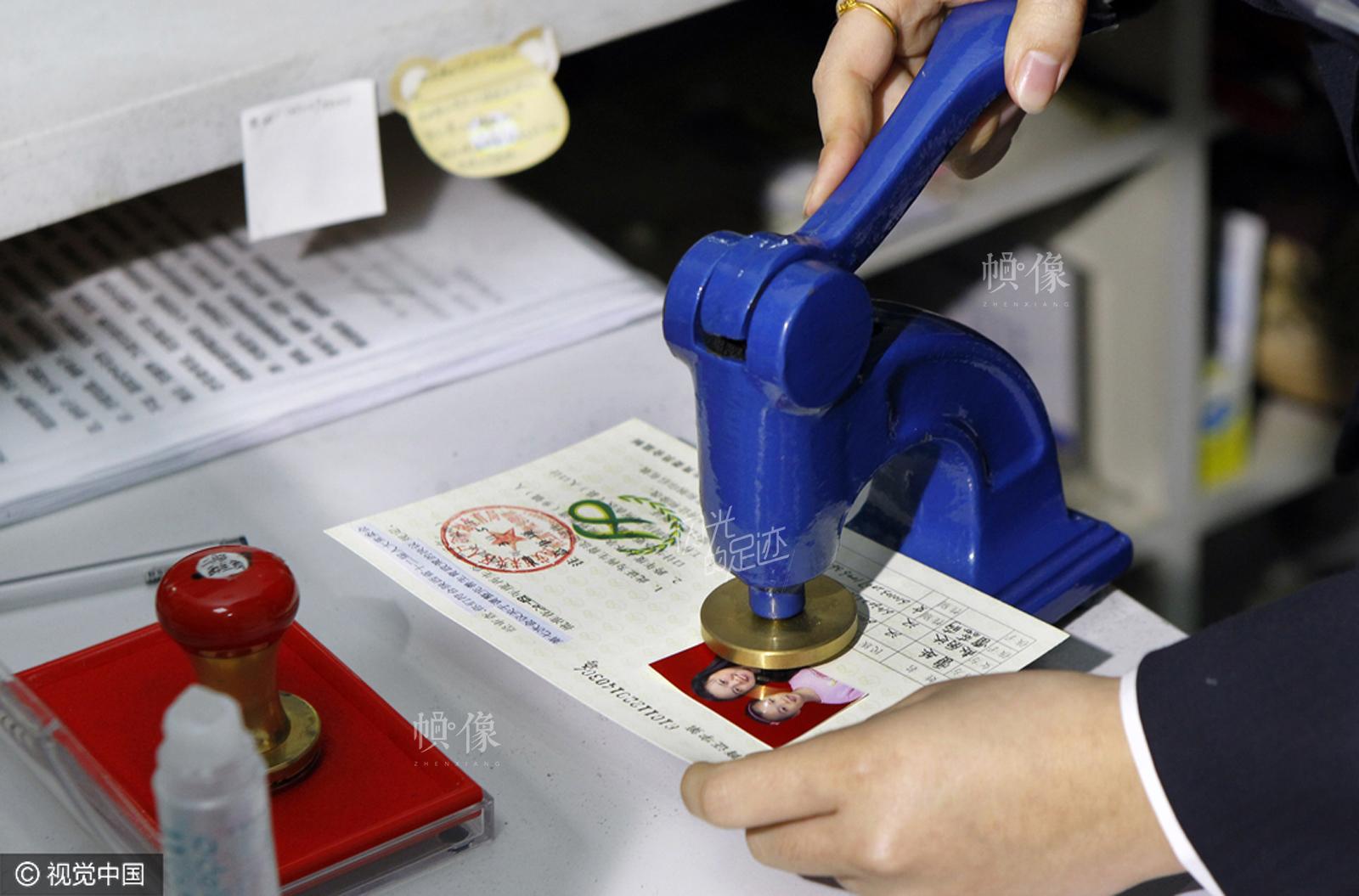 """2014年3月5日,西安市发放首张单独二孩生育证。 西安市未央区党务政务服务中心,人口计生部门工作人员在即将颁出的首张""""单独二孩""""生育证上盖章。 视觉中国"""