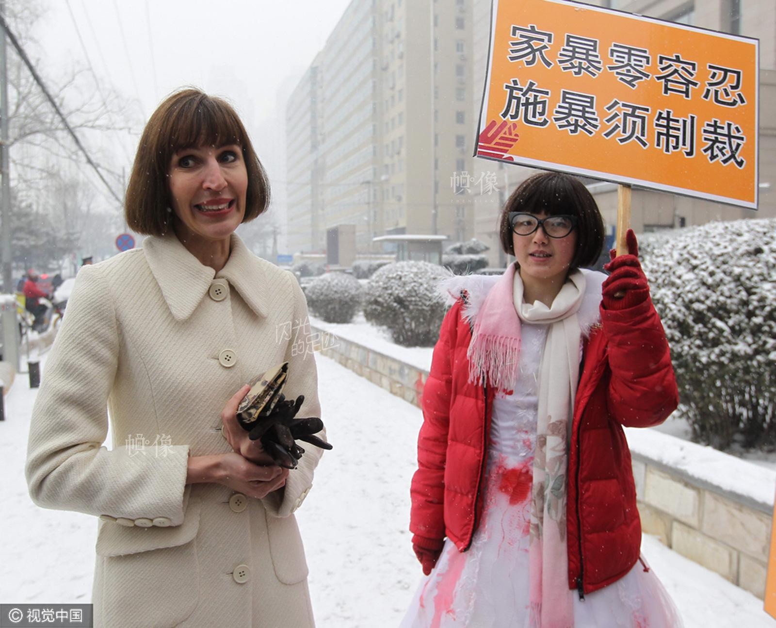 """2013年2月3日,北京,疯狂英语创始人李阳离婚案宣判。李阳妻子(Kim Lee)(左)  和举""""鄙视""""牌的反家暴民众。(视觉中国)"""