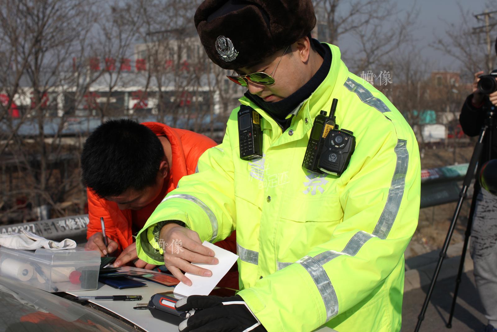 2017年2月27日,违法闯禁行货车司机在签字接受交警开出的罚单。中国网记者 赵超 摄
