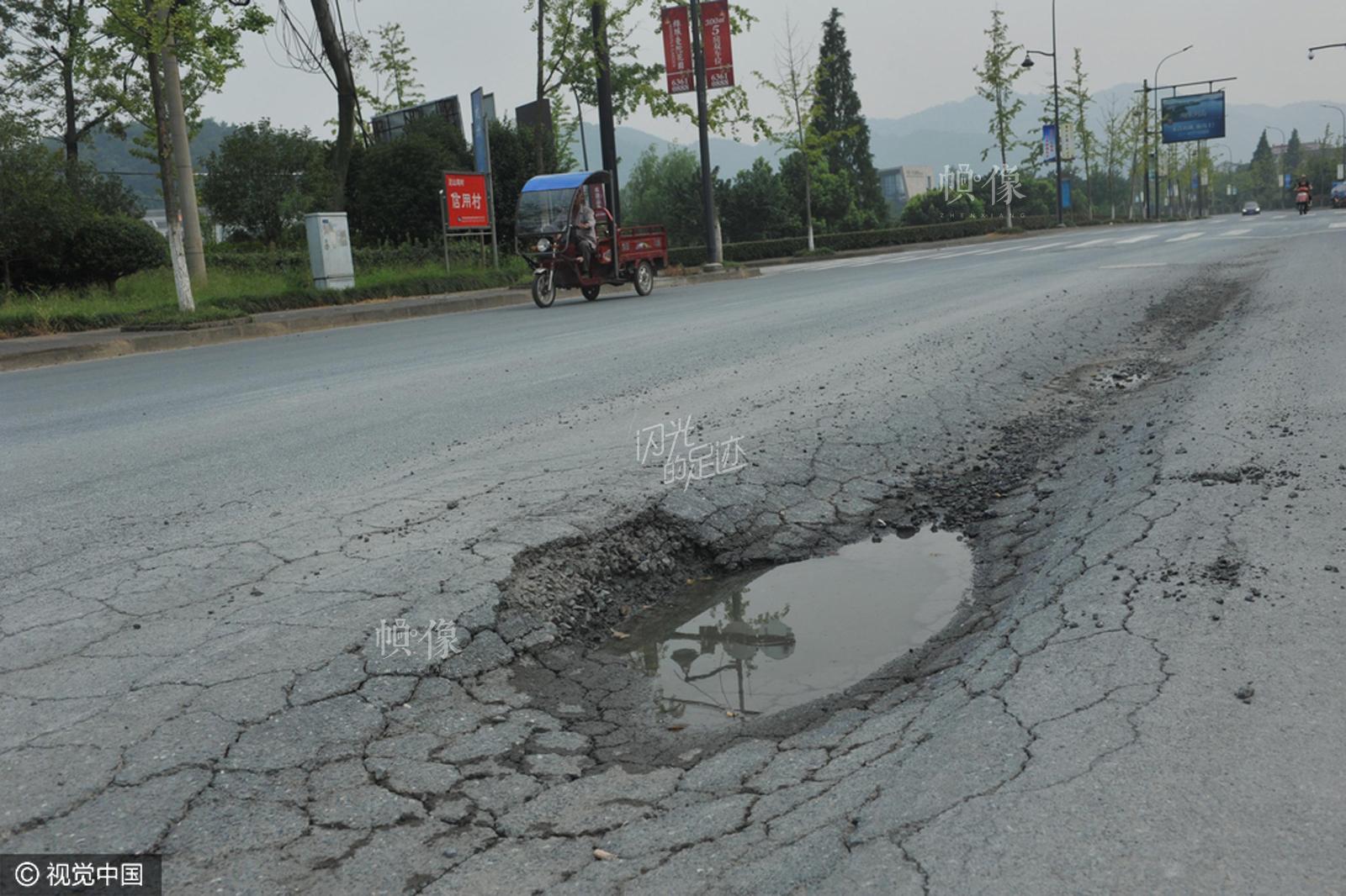 2015年8月30日,浙江省临安市圣元路上,一辆汽车从公路一侧的凹陷路面上驶过。据了解,出现路面凹陷的原因是周边常有超载工程车通过此地。视觉中国