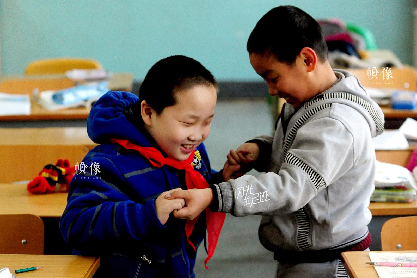 10岁的张伟患有先天性脑瘫,经过两次手术后,经帮助后可以简单的行走。2010年9月,他成了沈阳铁路第四小学二年二班的一名学生。图为张伟在同学的帮助下锻炼行走。(视觉中国供图)