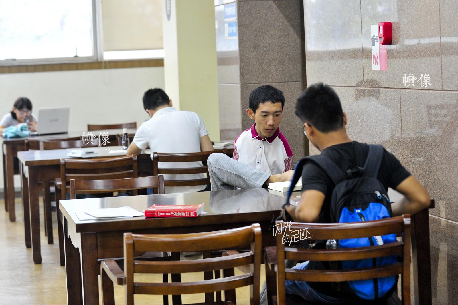 2015年9月14日,成都,无臂大学生彭超迎来了自己的大学生活,洗漱叠被子全都自己来。图为彭超在图书馆学习。(视觉中国)