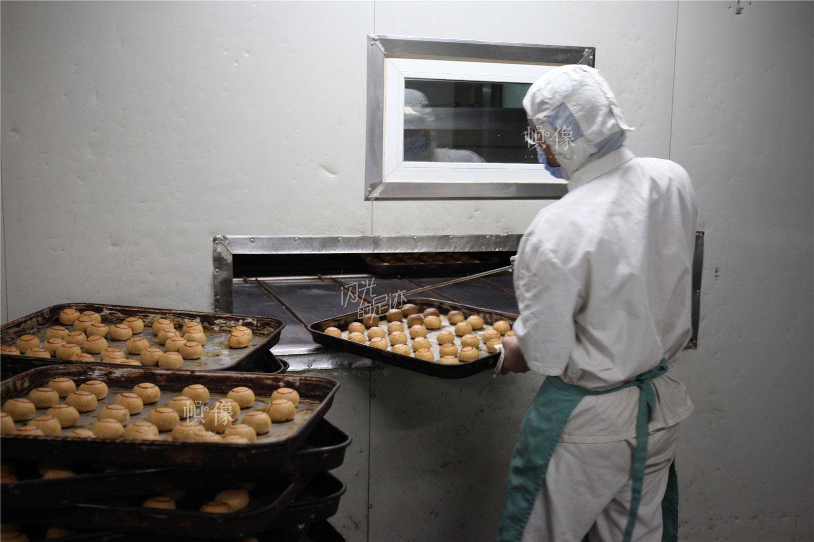 2017年3月2日,北京稻香村生产加工车间,工人正在处理刚出炉的糕点。中国网记者 高南 摄