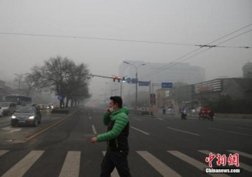 资料图:一名戴着口罩的行人走在北京街头。中新社记者 张浩 摄