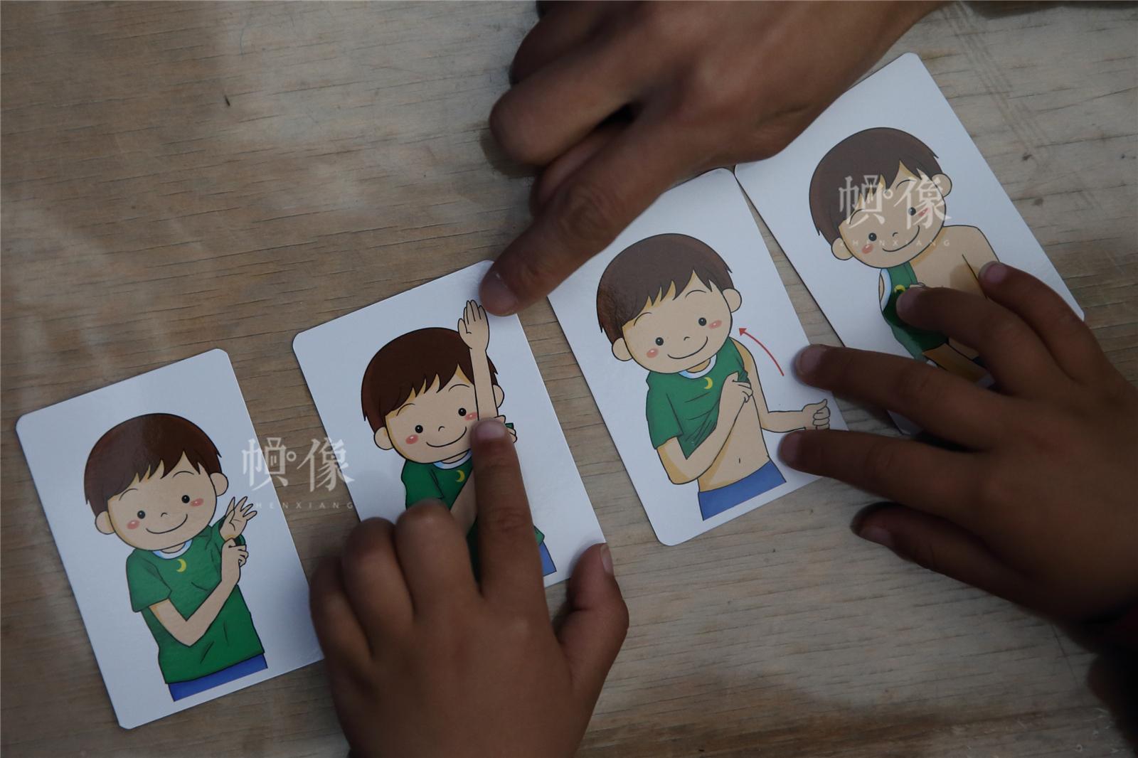 2017年3月27日,北京星星雨教育研究所,5岁的自闭症孩子源源在母亲的陪伴下,进行图画顺序训练。中国网记者陈维松 摄