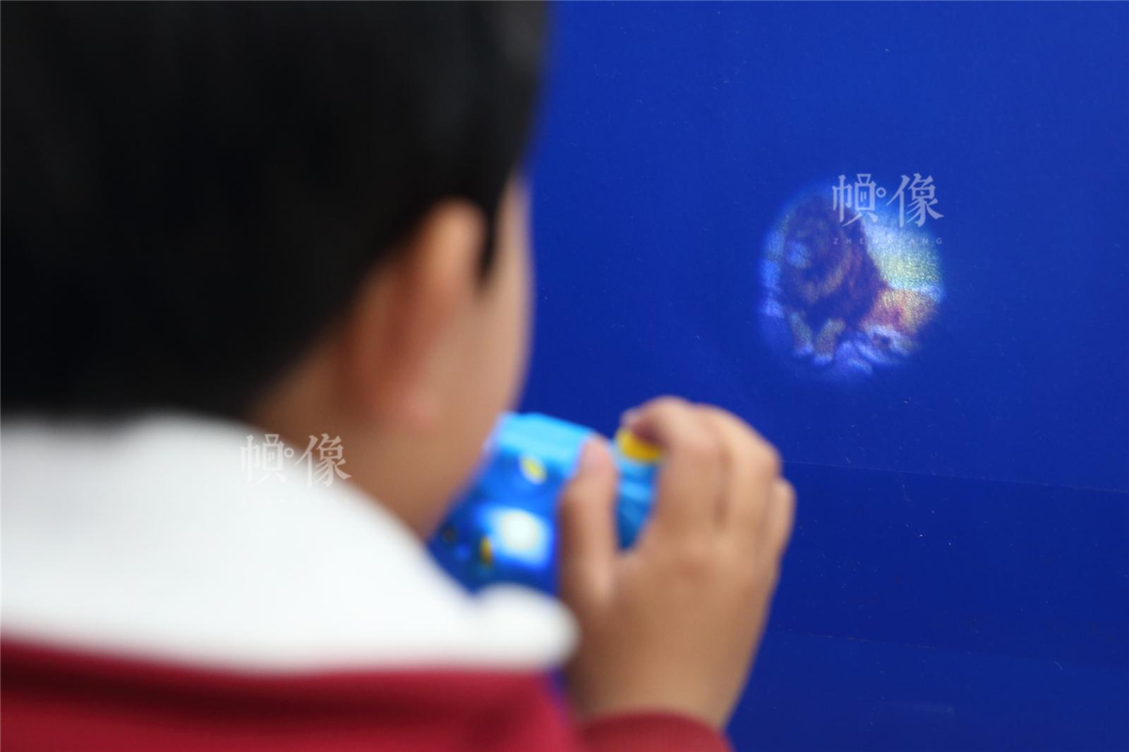 2017年3月27日,北京星星雨教育研究所,5岁的自闭症孩子源源在玩一个玩具相机。中国网记者陈维松 摄