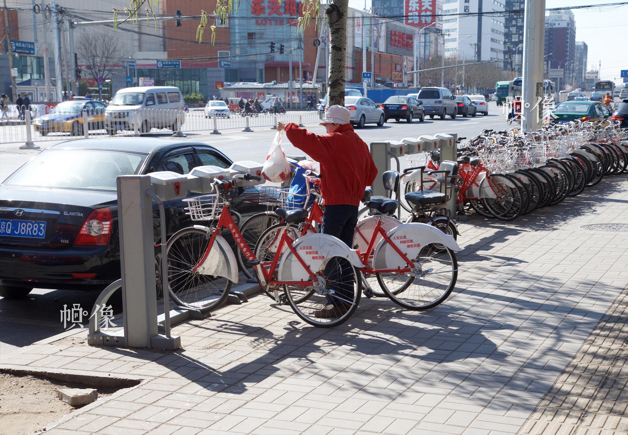 2017年3月27日,一名年长的市民在使用北京市政公共自行车。由于新兴的共享单车更多依靠智能移动设备,老年用户似乎更青睐于传统的市政公共自行车。中国网记者 高南 摄