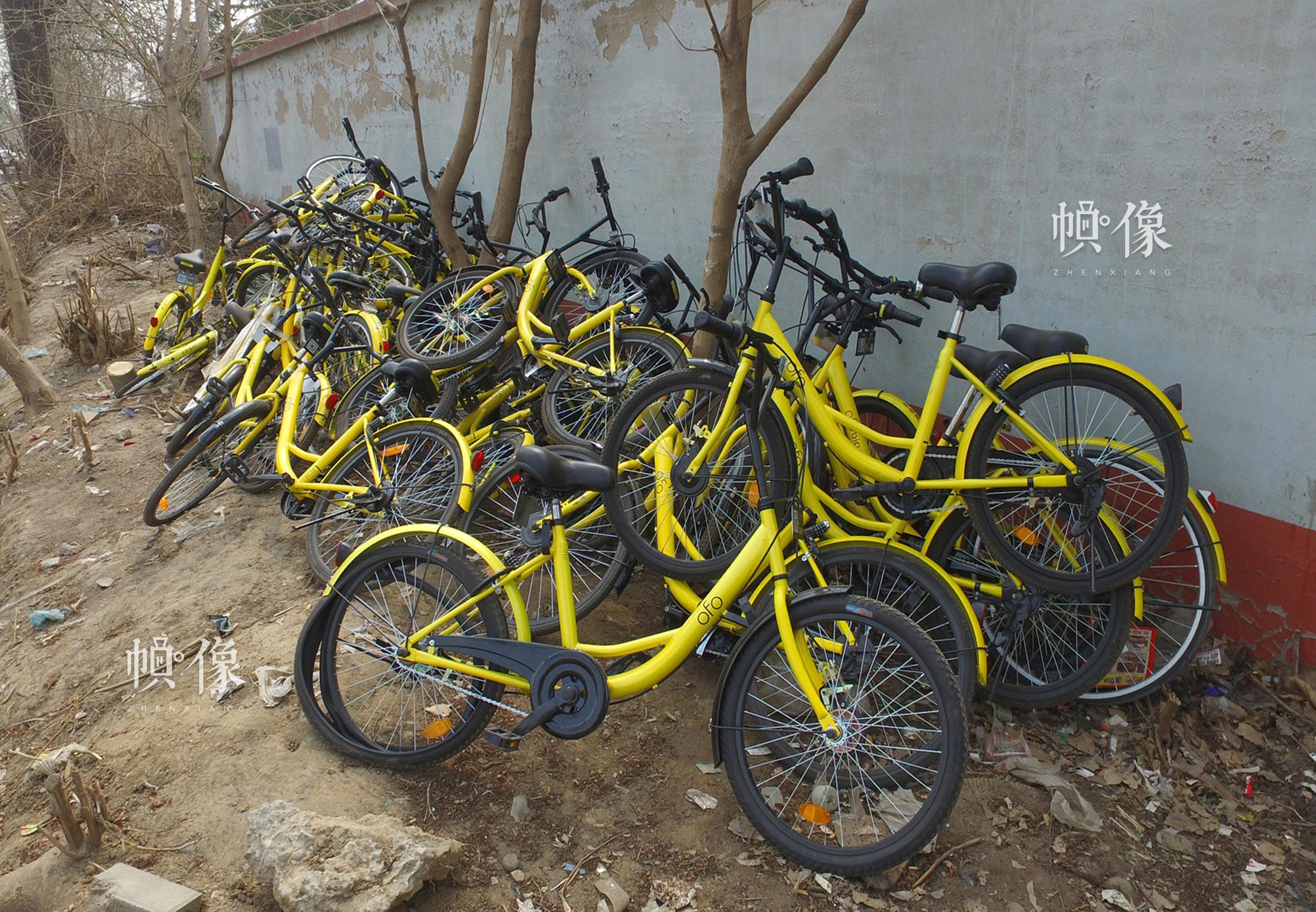 大量损坏的共享单车被堆放在墙角。中国网记者 高南 摄