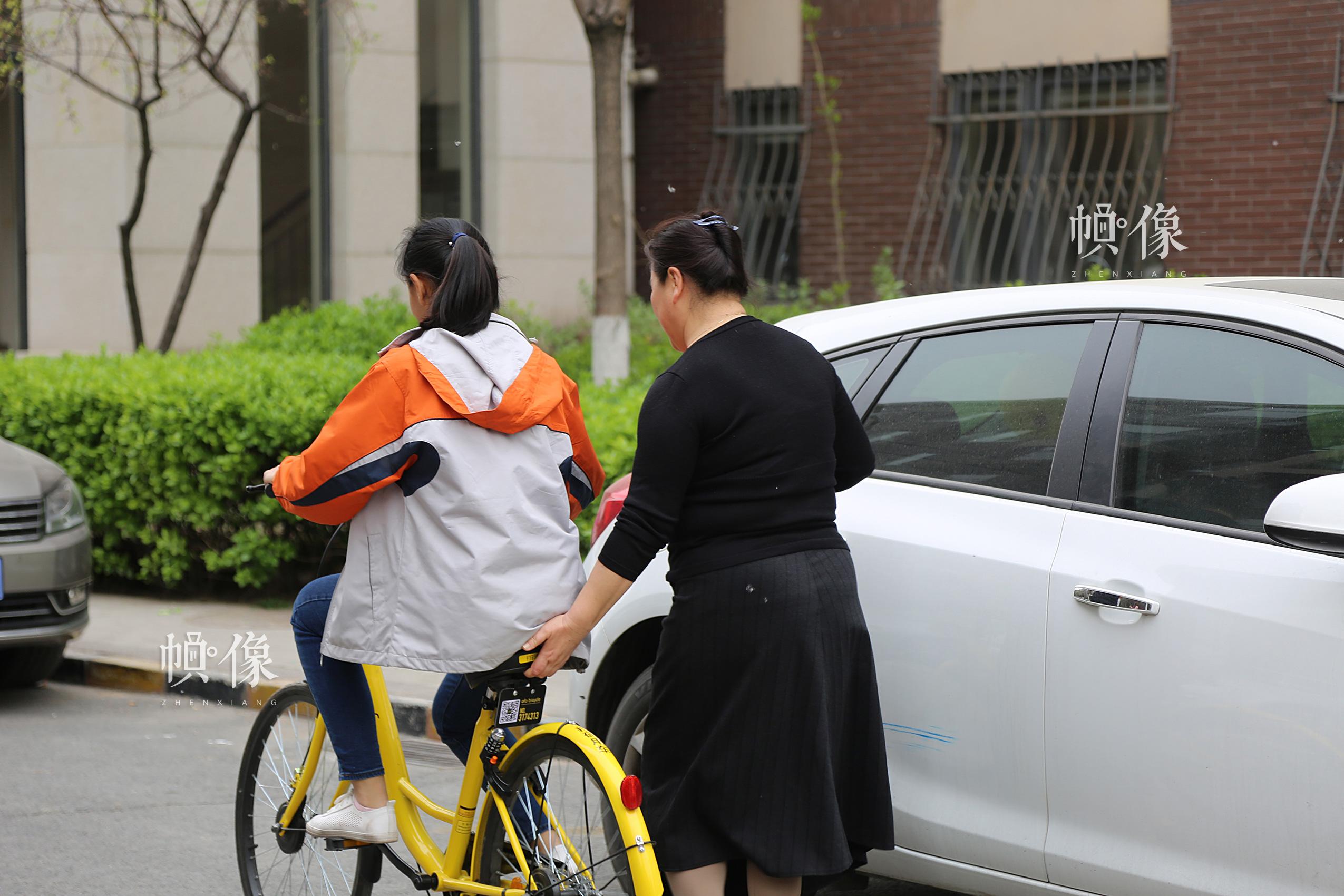 2017年4月8日,北京,德乾尕毛在小区骑自行车,助养妈妈在旁边帮她扶着。中国网记者 黄富友 摄