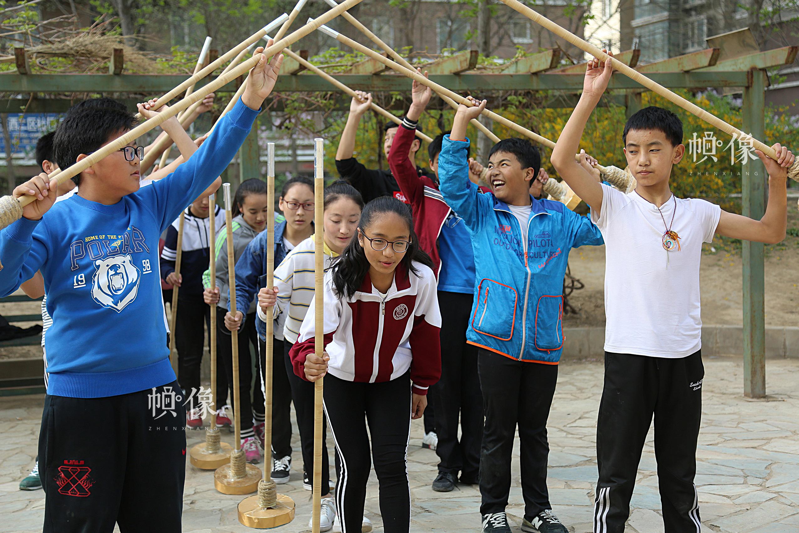 """2017年4月9日,学生们正在排练舞蹈打阿嘎。打阿嘎是一种藏族传统的屋顶或是屋内地面的修筑方法,利用当地特有的被称之为""""阿嘎土""""的泥土和碎石加上水混合后铺于地面或屋顶,再以人工反复夯打使地面、屋顶坚实、平滑、不渗漏水。打阿嘎时工人分成两队,边打边唱曲调悠扬的劳动号子,跟随着歌声的节奏手脚并用,上下整齐地夯打地面,场面壮观,是藏族的独特民俗之一。中国网记者 焦源源 摄"""