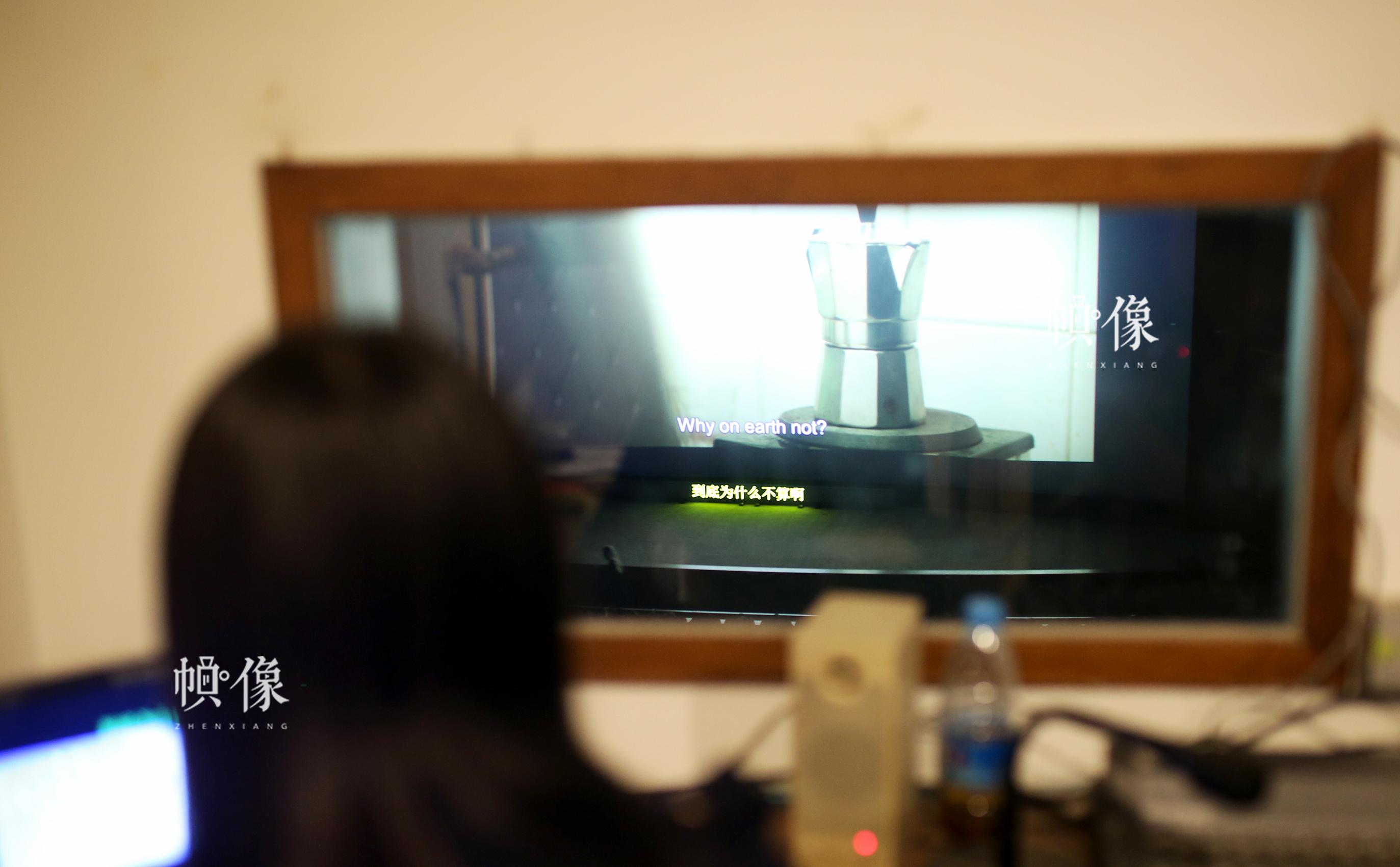 周立烨透过身侧的玻璃看着电影银幕,为电影加中文字幕。中国网记者 焦源源 摄