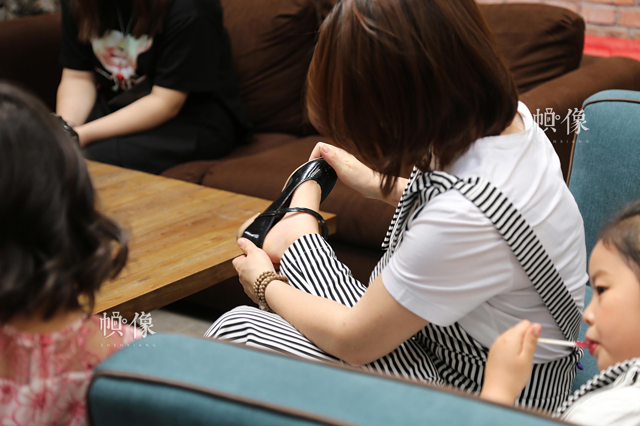 拍照前,李春晓为大女儿试穿挑选的鞋子。中国网记者黄富友 摄