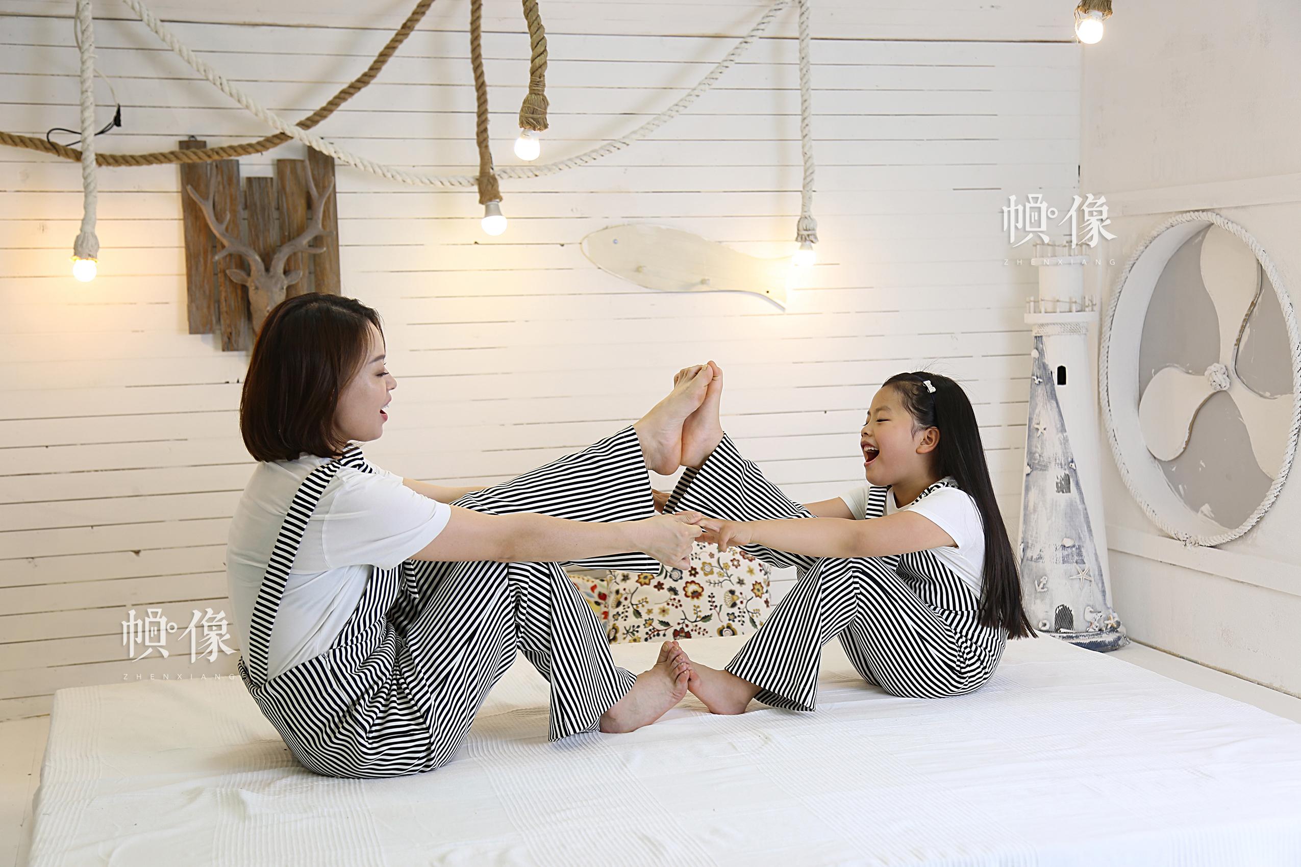 李春晓与大女儿合影,母女俩将平时在家练瑜伽的动作也带到了摄影棚。中国网记者黄富友 摄