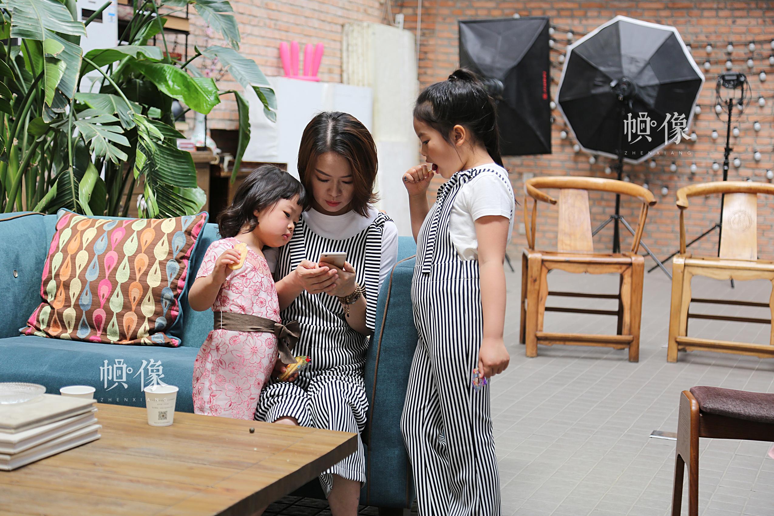 两个女儿围在李春晓身边,看妈妈刚才给她们拍的照片。中国网记者黄富友 摄