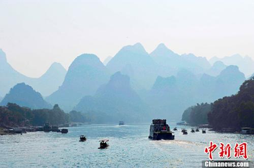 资料图:游人乘坐游船行驶在桂林漓江上面游玩观赏美丽的漓江风光,呈现烟雨漓江的画卷。胡雁 摄