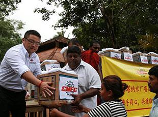 在斯里兰卡科伦坡附近的亚巴拉鲁瓦村,中国机械设备工程股份公司阿塔纳水厂项目组工作人员(左一)为灾民分发赈灾物资