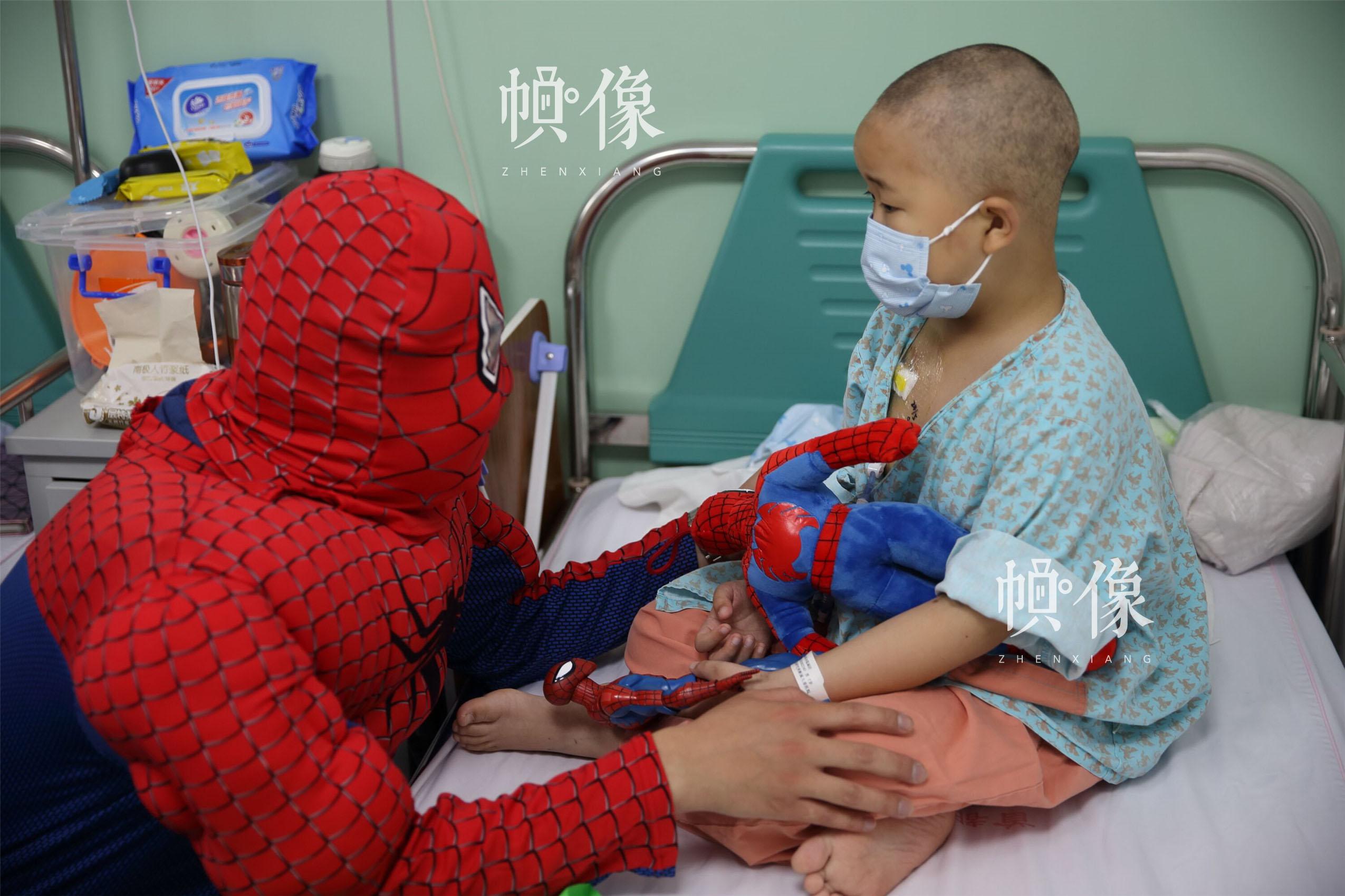 """2017年5月26日,北京首都儿科研究所,""""你是我的英雄""""活动结束后,男护士季长绪穿着""""蜘蛛侠""""的衣服,来到病房看望天佑。他说,看到孩子的难受,看到孩子的坚强,自己很受启发。季长绪希望通过自己的工作,鼓励孩子们如心中的英雄人物一般,勇敢面对人生中暂时的艰难时刻。中国网记者 陈维松 摄"""