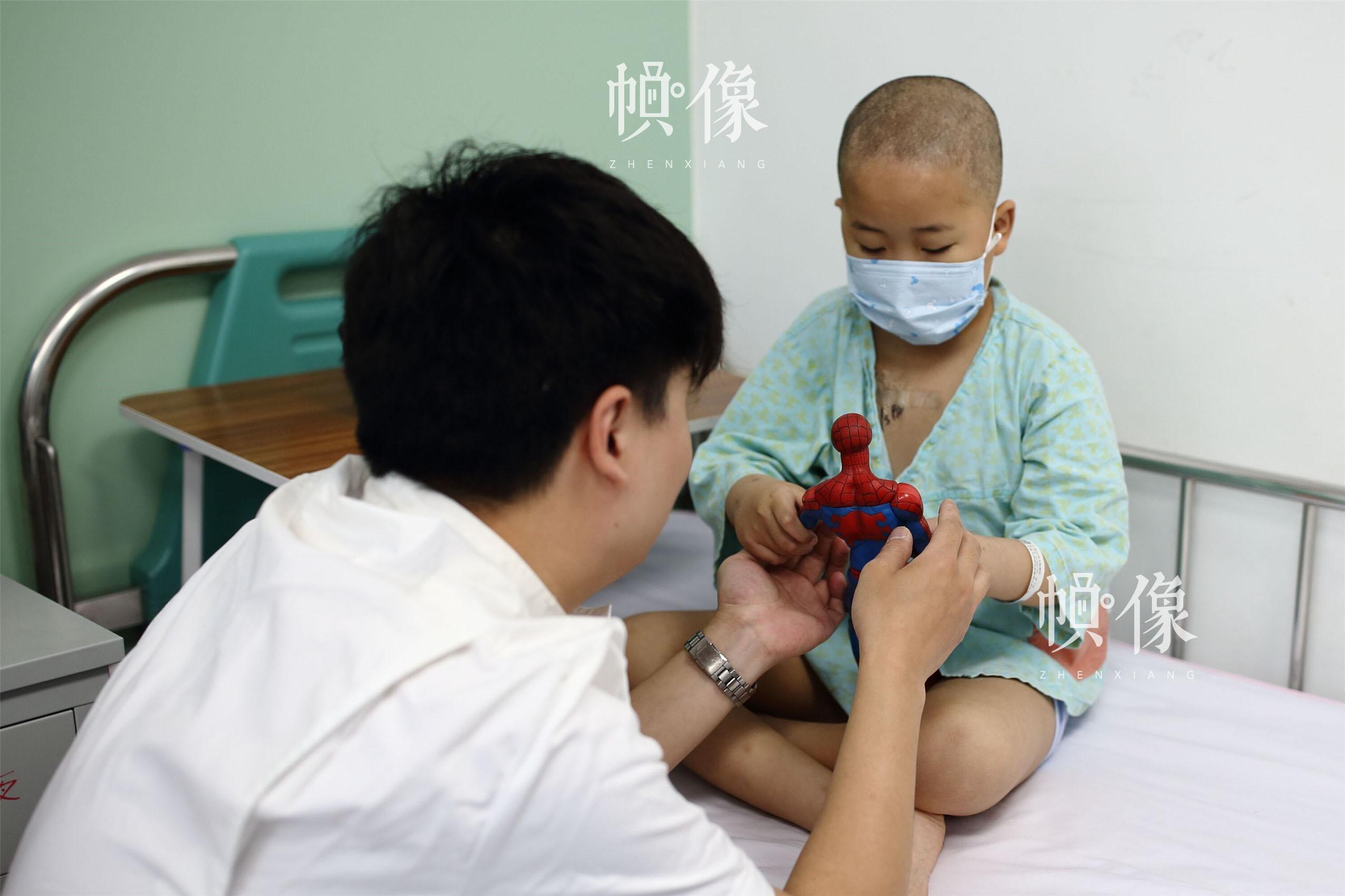 """2017年5月24日,北京首都儿科研究所,男护士季长绪给白血病患儿天佑一个蜘蛛侠玩具。刚入院时一天要抽血数次,给年幼的天佑造成阴影。""""他天天就想着这个事,经常说'妈妈,我是不是还要抽血?'""""天佑的母亲海燕说。看到孩子的低迷,知道天佑喜欢""""蜘蛛侠""""的季长绪,给孩子送了这个玩具,希望能鼓励他勇敢接受治疗。中国网记者 陈维松 摄"""