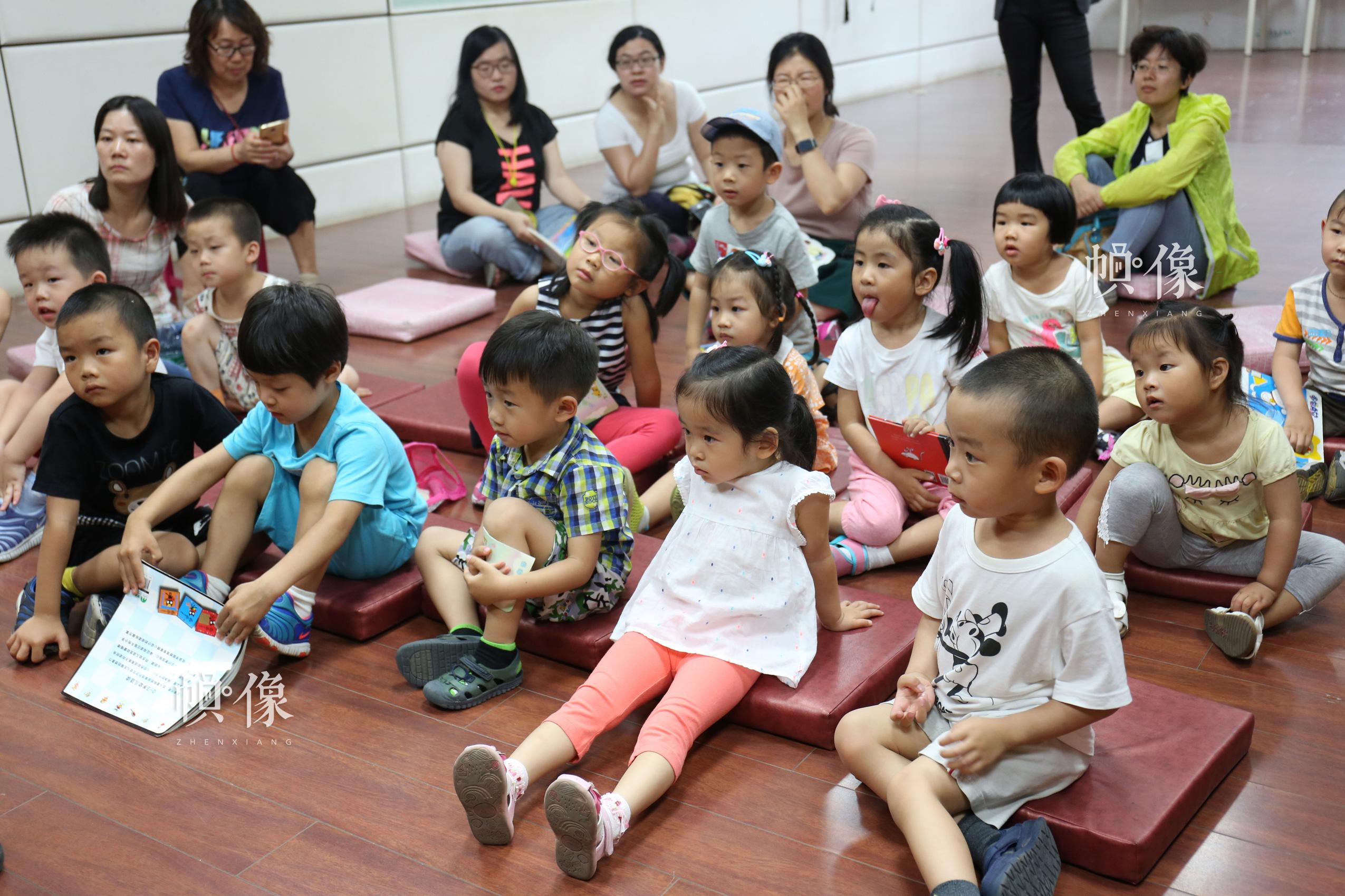 图为神态各异的听工作人员读书的小朋友。 中国网记者 吴佳潼 摄