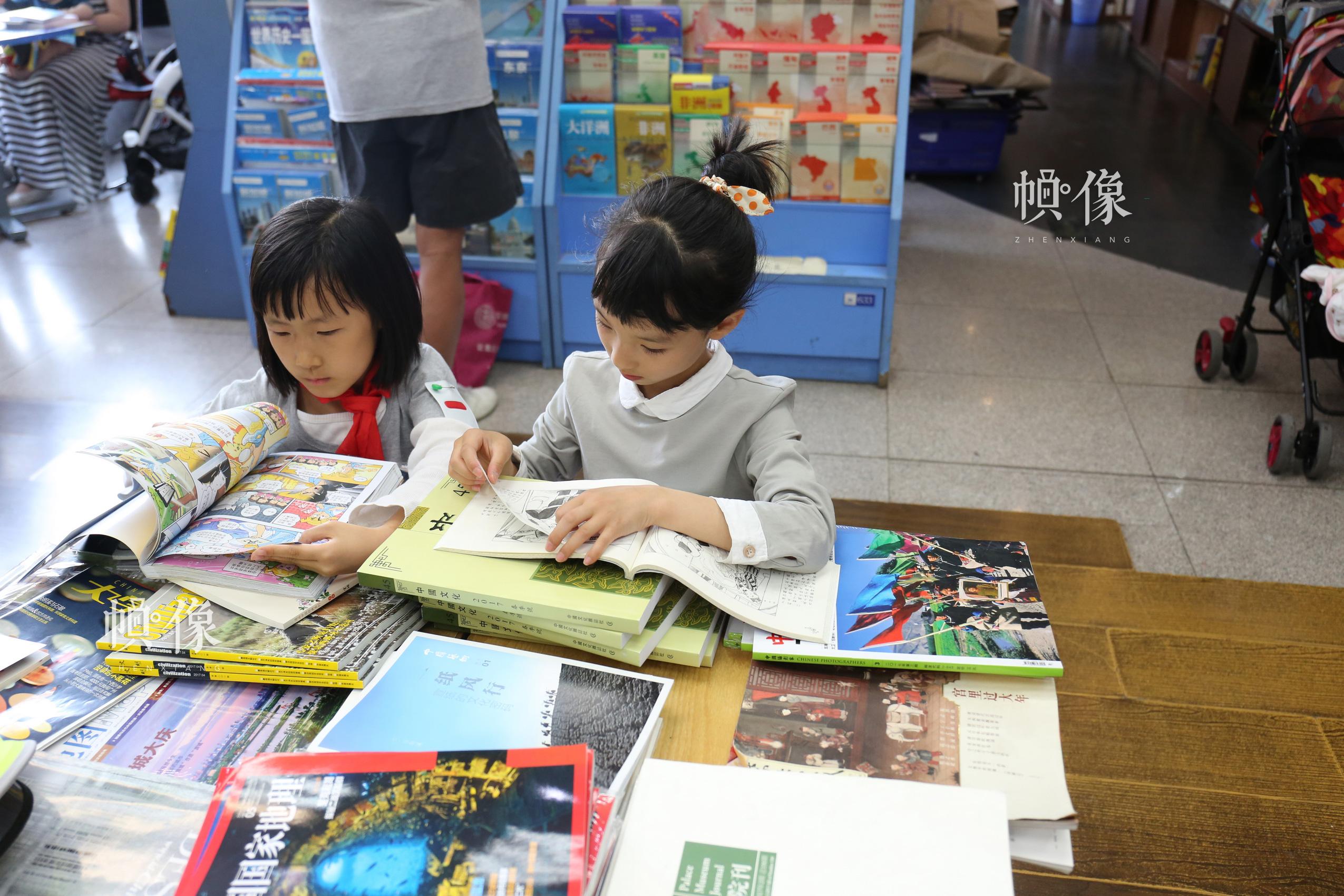 5月23日,北京三联书店美术馆店,两名刚下课的小朋友在读书。 中国网记者 赵超 摄