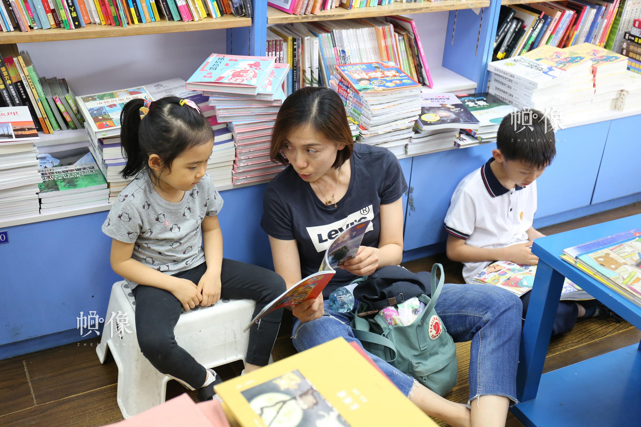 5月23日,北京三联书店美术馆店,一位妈妈给女儿读书。 中国网记者 赵超 摄
