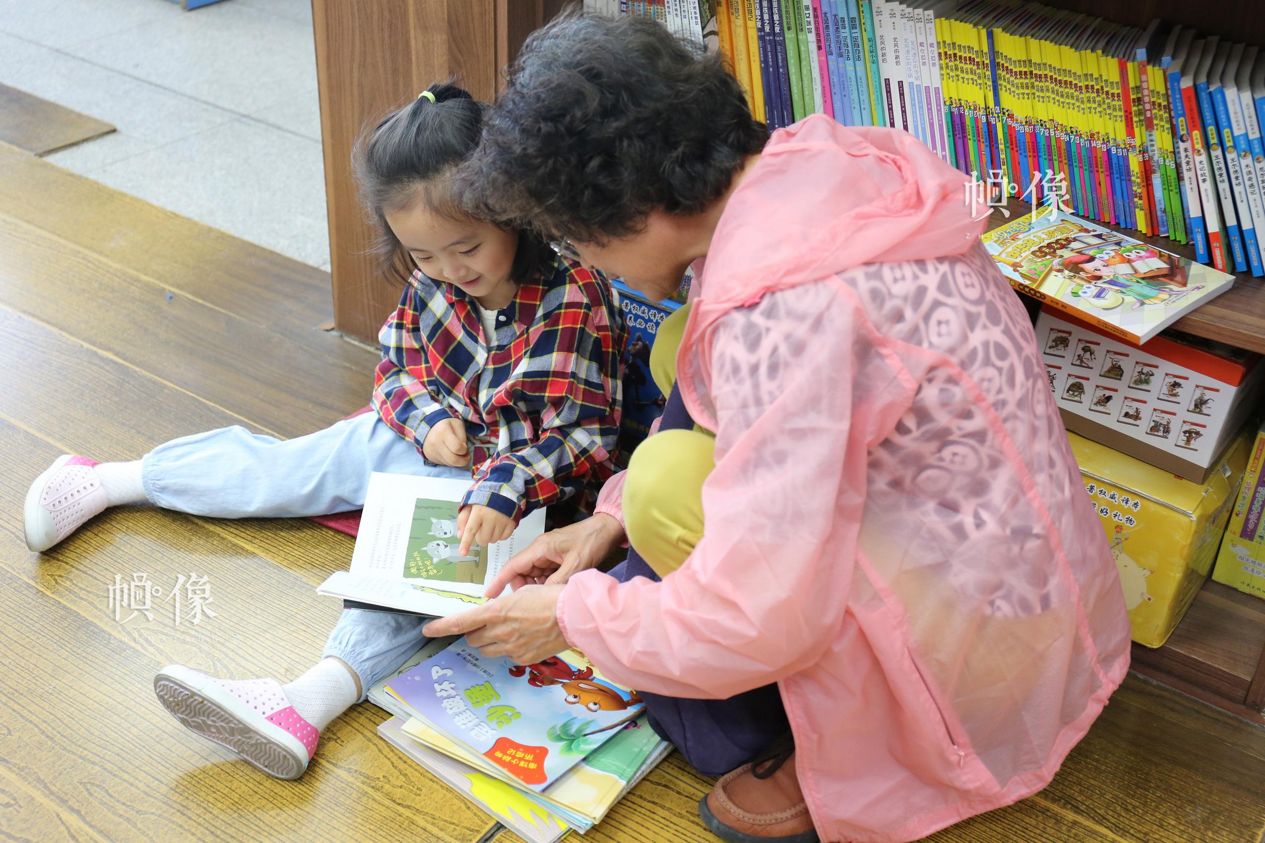 5月23日,北京三联书店美术馆店,一位老者给孙女读书。 中国网记者 赵超 摄