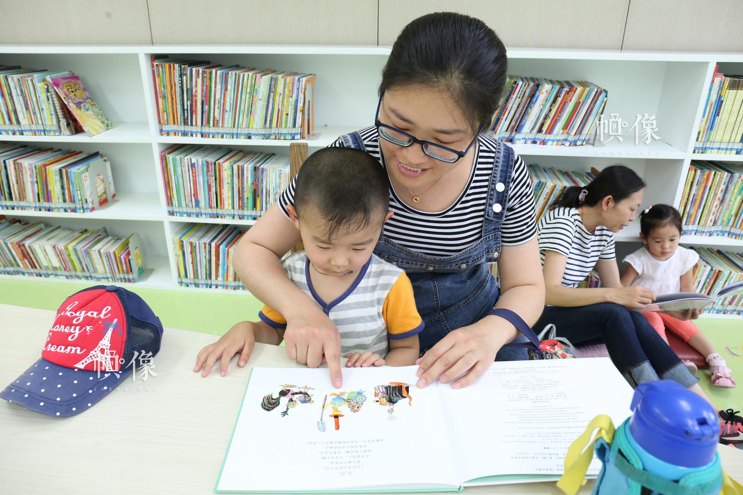 5月26日,北京国家图书馆,一位妈妈和儿子一起看书。 中国网记者 赵超 摄