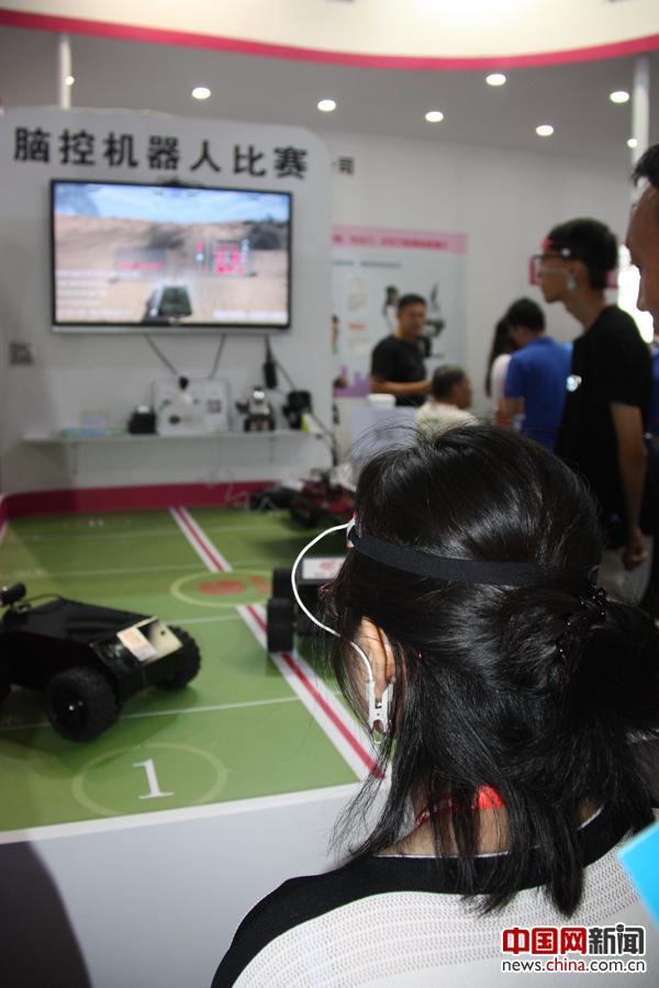 """2017年6月8日,在第二十届北京国际科博会上,头戴脑波发带的一名男青年(远处站立者)和一名女青年在参加""""脑控机器人""""比赛。据参展商介绍,这种设备可以使人们在娱乐游戏中学会控制自己的情绪,释放压力,提高大脑的应激能力,并快速消除脑疲劳。 中国网记者 苏向东 摄影"""