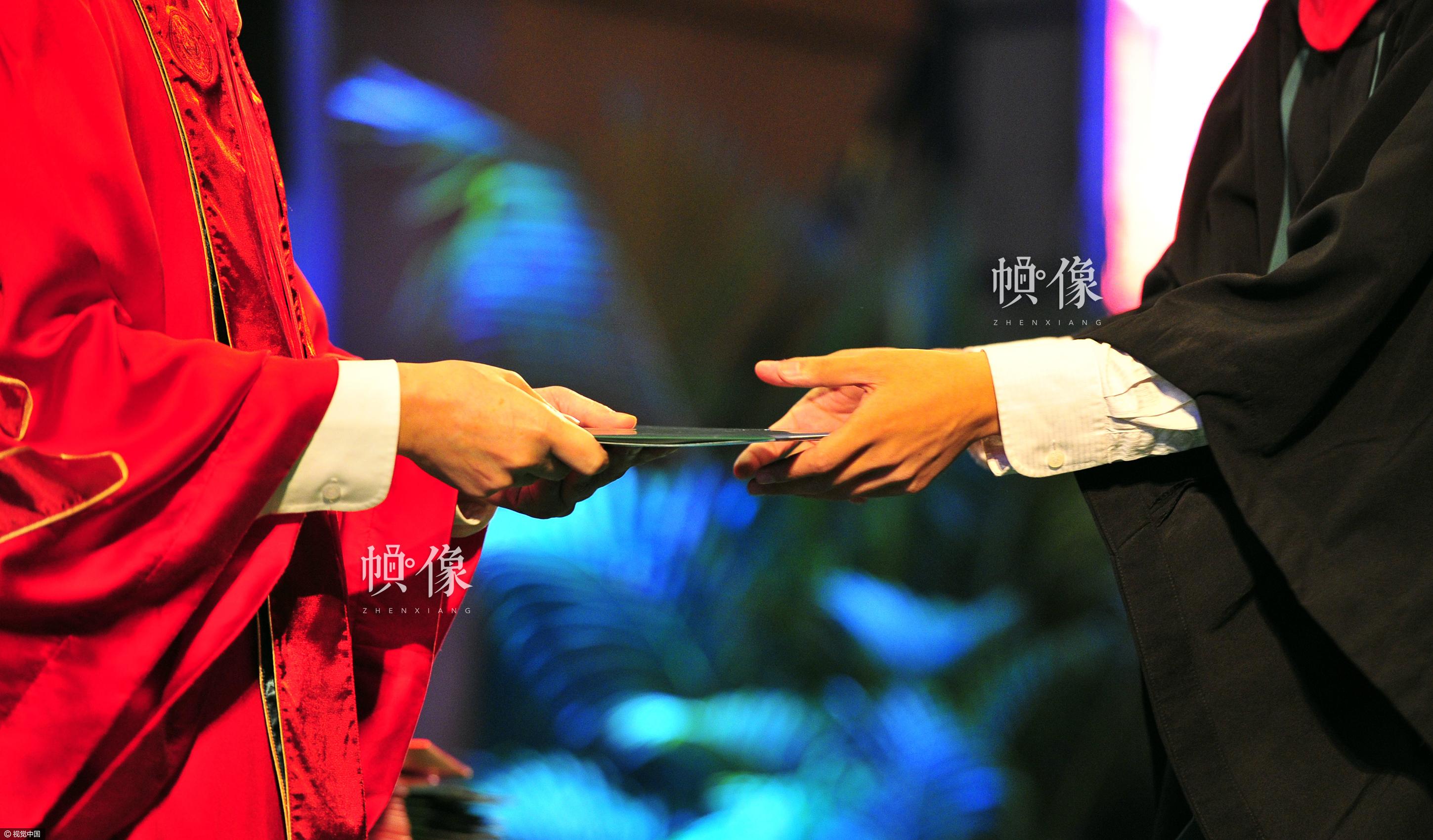 2012年6月28日,广州中山大学举行2012届毕业典礼,校长许宁生与毕业学生握手,并颁发毕业纪念册。视觉中国供图