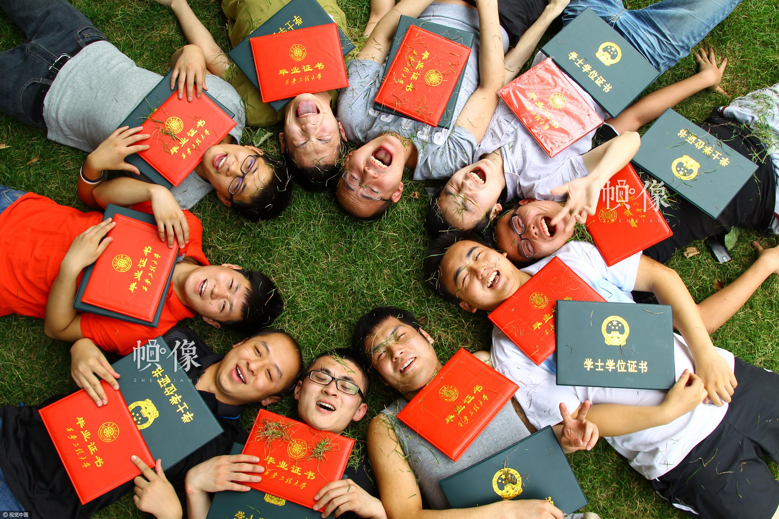 2012年6月28日,西安工程大学校园内,2008届艺术设计班的几位同学拿着毕业证和学位证躺在草地上。吕松杨是其中一位,他说现在的大学生多得犹如地上的青草,但我们愿从草根做起,拾级而上为梦想拼搏。视觉中国供图