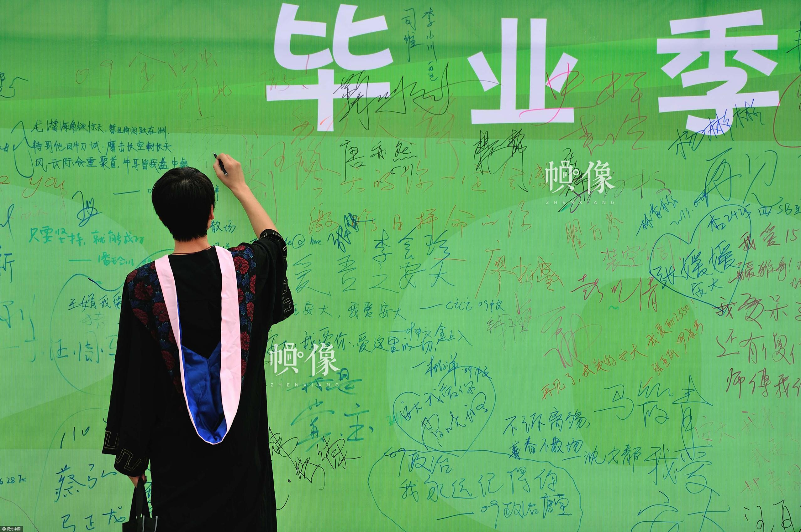 2013年6月28日,合肥,安徽大学,一位毕业生在毕业版上签名。视觉中国供图