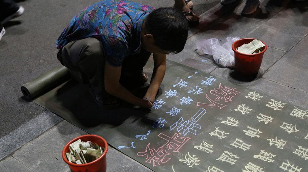 51岁'励志大叔'靠残肢写粉笔字穿梭200多个城市求生
