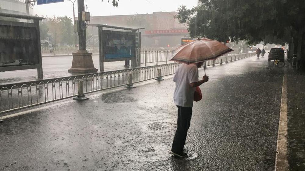 北京清晨现大雨 民众冒雨出行
