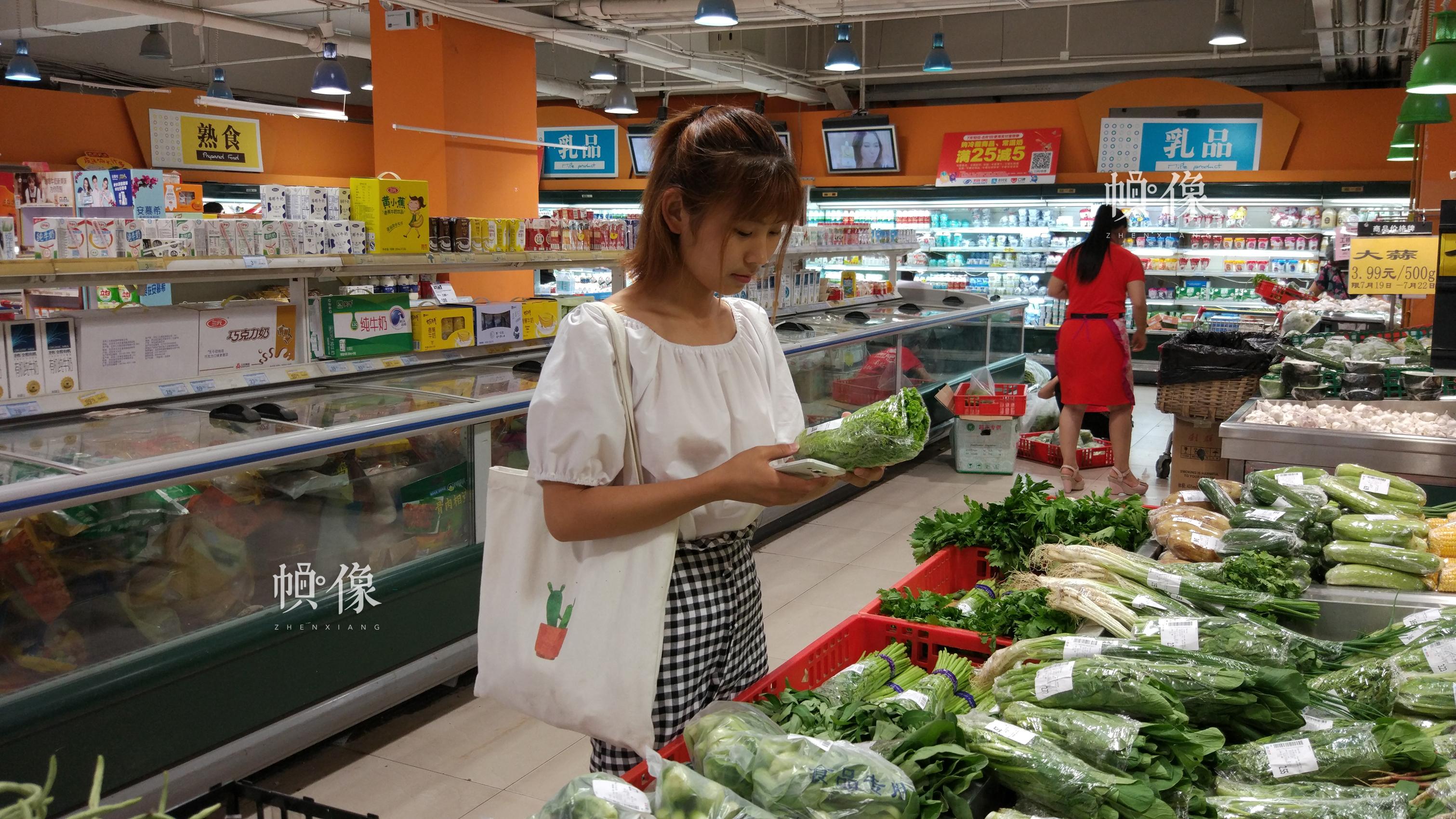 2017年7月19日,消费者在北京某超市售菜专柜前选菜。中国网记者 赵超 摄