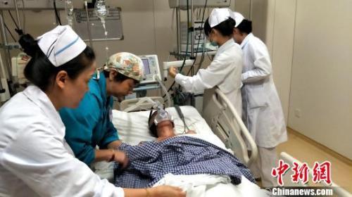 资料图:医护人员为患者插上医疗仪器。徐志雄 摄
