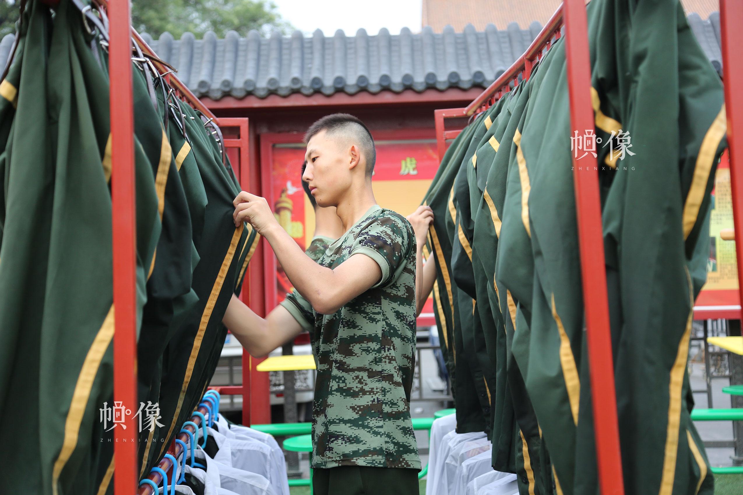 每一次升旗结束,国旗护卫队队员的礼服都浸满了汗水,图为国旗护卫队员整理军装。中国网记者 黄富友 摄