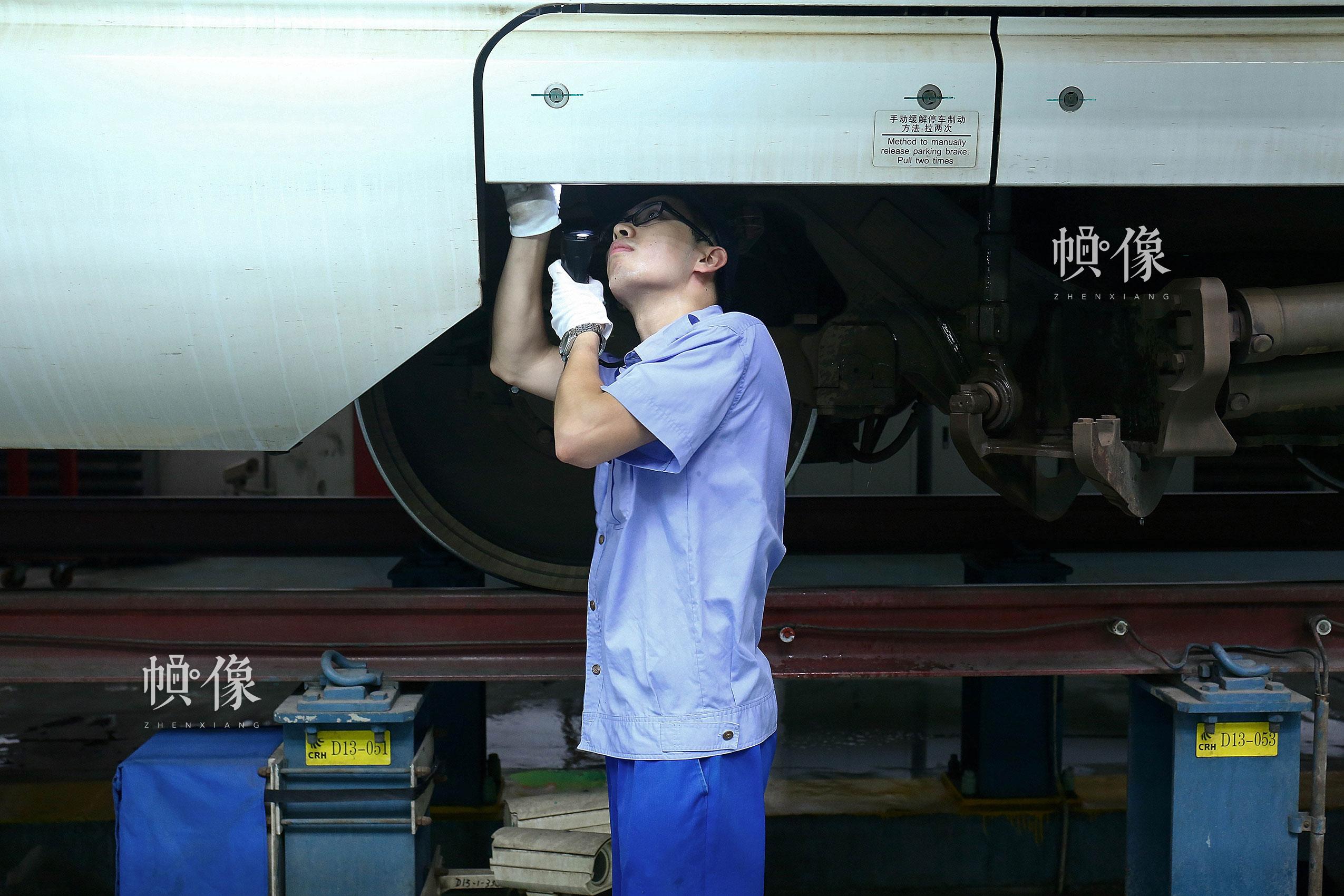 作业人员王腾检查车辆裙板状态。中国网记者 黄富友 摄